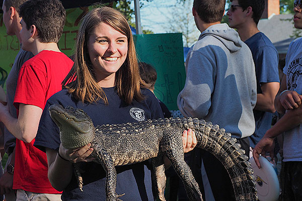 Female student holding an alligator