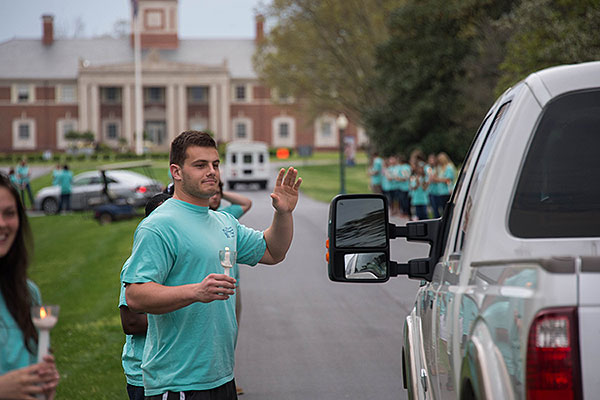 Student waving to donors as they drive on campus