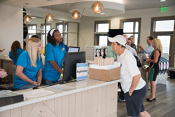 01 - Students helping a tennis player at the counter