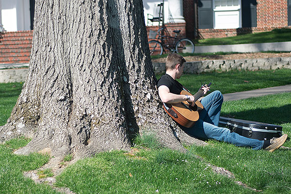 10 - Male student playing guitar under a tree