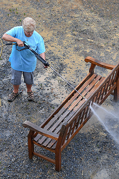 08 - Woman pressure washing a bench