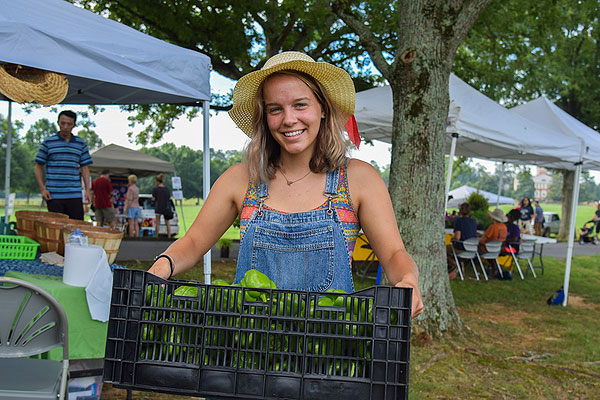 14 - Girl in hat carrying crate of green peppers