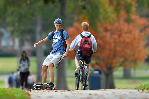 02 - Students walking, riding bikes and skateboarding through the fall color