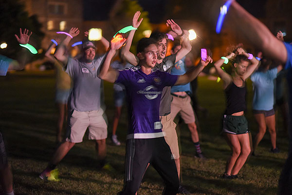 12 - New students doing jumping jacks with glow sticks at night